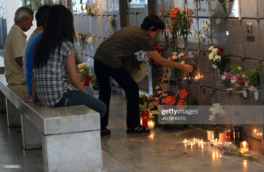 People visit the graves of relatives and loved ones in Manila on November 1, 2012. Millions across the Philippines visited cemeteries to pay respects to their dead, in an annual tradition that combines Catholic religious rites with the country's penchant for festivity.