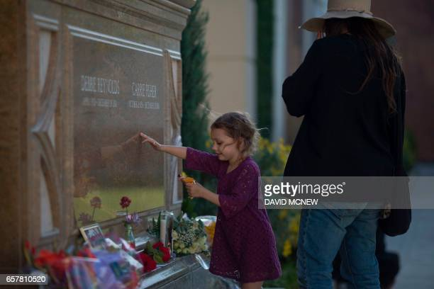 People visit the joint gravesite for Carrie Fisher and her mother Debbie Reynolds following a public memorial on March 25 2017 in Los Angeles...