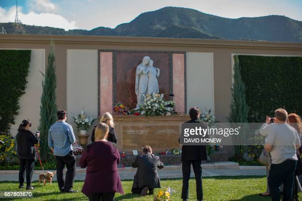 People visit the joint gravesite of Carrie Fisher and her mother Debbie Reynolds following a public memorial on March 25 2017 in Los Angeles...