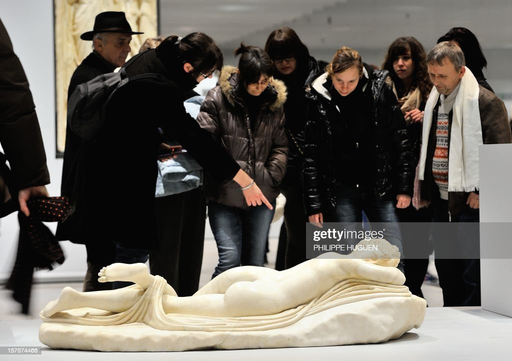 People visit the Louvre Museum on the first day of its opening to the public on December 4, 2012 in Lens, northern France. The Louvre museum opened a new satellite branch among the slag heaps of a former mining town Tuesday in a bid to bring high culture and visitors to one of France's poorest areas. Greeted by a group of former miners in overalls and hardhats, President Francois Hollande inaugurated today the Japanese-designed glass and polished-aluminium branch of the Louvre in the northern city of Lens. The 150 million euro ($196 million) project was 60 percent financed by regional authorities in the Nord-Pas-De-Calais region, on the English Channel and the border with Belgium. AFP PHOTO PHILIPPE HUGUEN