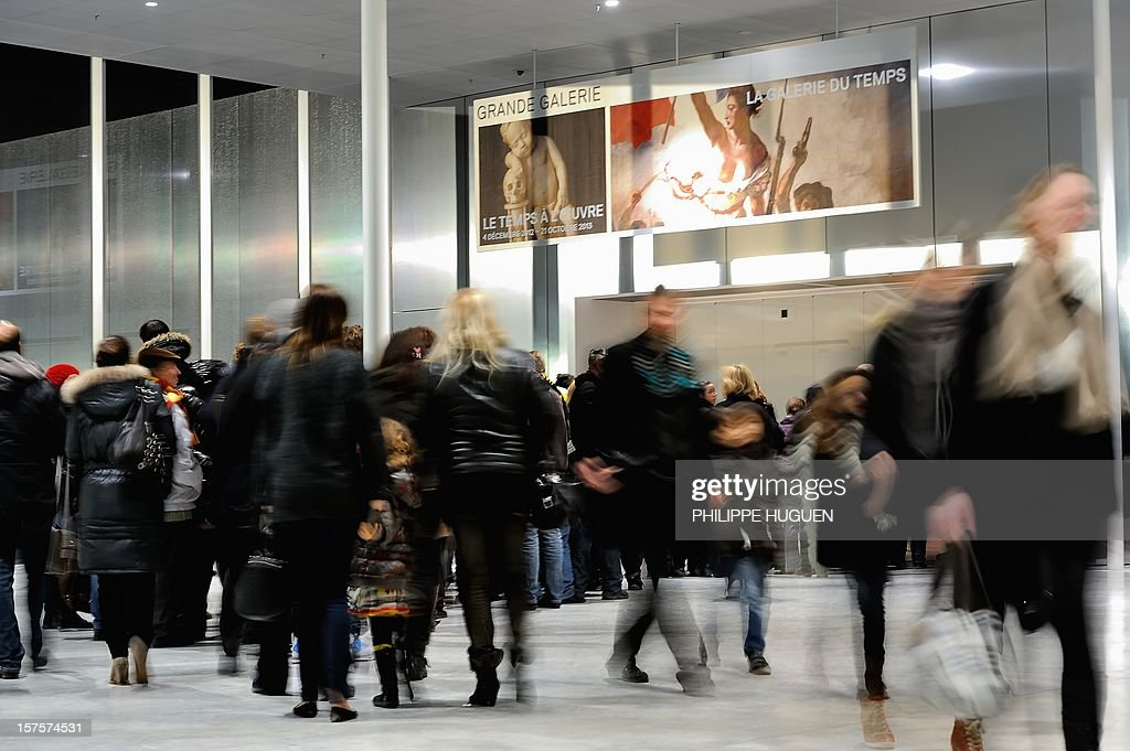 People visit the Louvre Museum on the first day of its opening to the public on December 4, 2012 in Lens, northern France. The Louvre museum opened a new satellite branch among the slag heaps of a former mining town Tuesday in a bid to bring high culture and visitors to one of France's poorest areas. Greeted by a group of former miners in overalls and hardhats, President Francois Hollande inaugurated today the Japanese-designed glass and polished-aluminium branch of the Louvre in the northern city of Lens. The 150 million euro ($196 million) project was 60 percent financed by regional authorities in the Nord-Pas-De-Calais region, on the English Channel and the border with Belgium.
