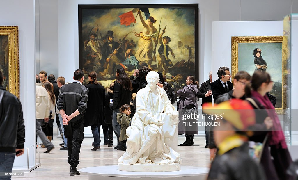 People visit the Louvre Museum on the first day of its opening to the public, on December 4, 2012 in Lens, northern France. The Louvre museum opened a new satellite branch among the slag heaps of a former mining town Tuesday in a bid to bring high culture and visitors to one of France's poorest areas. Greeted by a group of former miners in overalls and hardhats, President Francois Hollande inaugurated today the Japanese-designed glass and polished-aluminium branch of the Louvre in the northern city of Lens. The 150 million euro ($196 million) project was 60 percent financed by regional authorities in the Nord-Pas-De-Calais region, on the English Channel and the border with Belgium. In the background is seen 'La Liberte guidant le peuple' (Liberty Leading the People) by French painter Eugene Delacroix. AFP PHOTO PHILIPPE HUGUEN