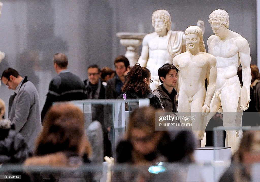 People visit the Louvre Museum on the first day of its opening to the public, on December 4, 2012 in Lens, northern France. The Louvre museum opened a new satellite branch among the slag heaps of a former mining town Tuesday in a bid to bring high culture and visitors to one of France's poorest areas. Greeted by a group of former miners in overalls and hardhats, President Francois Hollande inaugurated today the Japanese-designed glass and polished-aluminium branch of the Louvre in the northern city of Lens. The 150 million euro ($196 million) project was 60 percent financed by regional authorities in the Nord-Pas-De-Calais region, on the English Channel and the border with Belgium. AFP PHOTO PHILIPPE HUGUEN