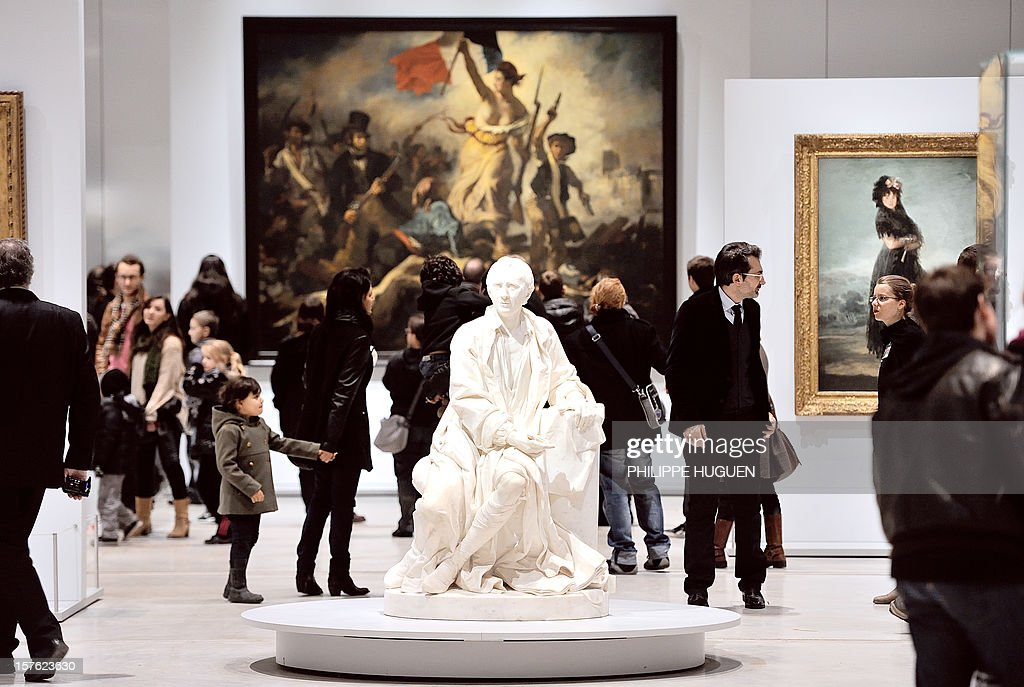 People visit the Louvre Museum on the first day of its opening to the public, on December 4, 2012 in Lens, northern France. The Louvre museum opened a new satellite branch among the slag heaps of a former mining town Tuesday in a bid to bring high culture and visitors to one of France's poorest areas. Greeted by a group of former miners in overalls and hardhats, President Francois Hollande inaugurated today the Japanese-designed glass and polished-aluminium branch of the Louvre in the northern city of Lens. The 150 million euro ($196 million) project was 60 percent financed by regional authorities in the Nord-Pas-De-Calais region, on the English Channel and the border with Belgium. In the background is seen 'La Liberte guidant le peuple' (Liberty Leading the People) by French painter Eugene Delacroix.