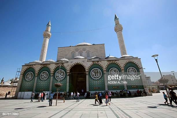 People visit the mausoleum of Jalal adDin Muhammad Rumi and the Selamiye mosque in Konya Central Anatolia region on August 17 2016 The face of...