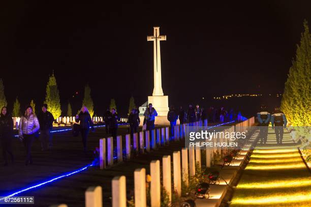 People visit the military cemetery of the Australian National Memorial in VillersBretonneux northern FRance with gendarmes patrolling on April 25...
