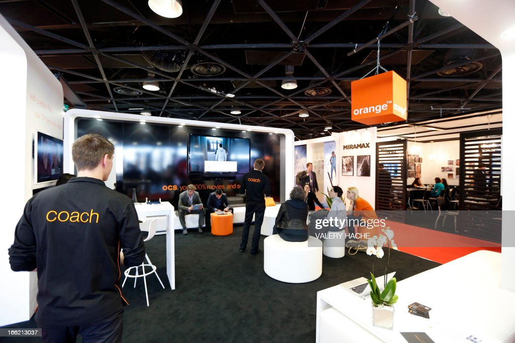 People visit the 'Orange' stand at the MIPTV one of the world's largest broadcasting and audio-visual trade show, on April 10, 2013 in Cannes, southeastern France . AFP PHOTO / VALERY HACHE