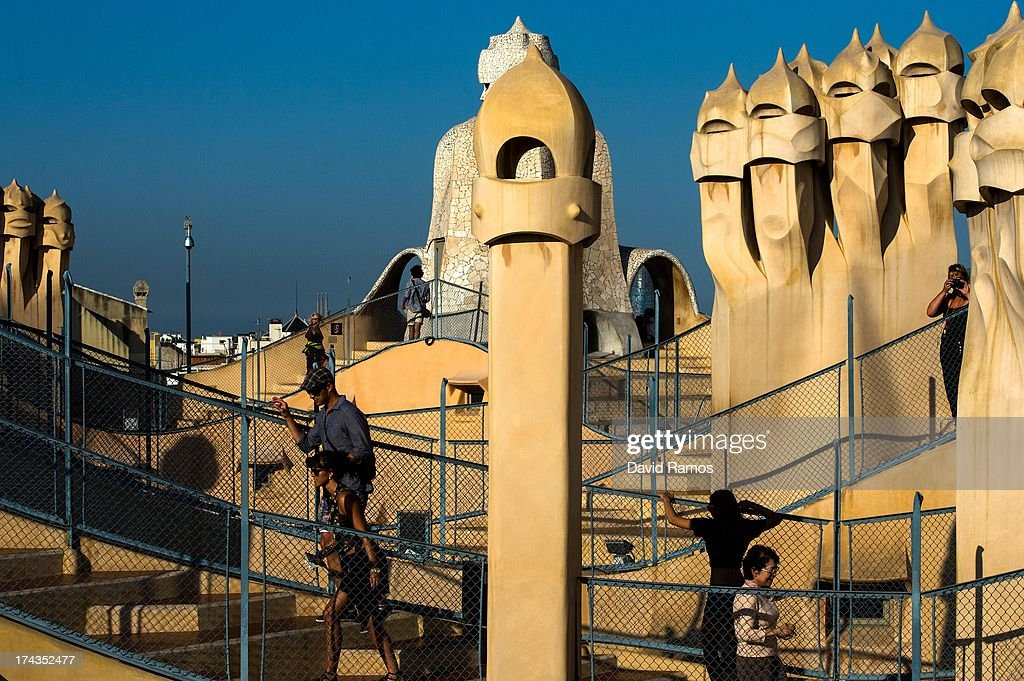 People visit the roof of Antoni Gaudi's building 'La Pedrera' or 'Casa Mila' on July 24, 2013 in Barcelona, Spain. Foreign visitors to Spain set a new record high in June surpassing six million tourists for the first time ever and climbing by 5.3 percent since June 2012.