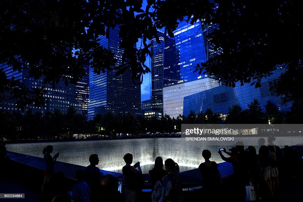 TOPSHOT - People visit the South Pool, which marks the former site of the South Tower of the World Trade Center, at Ground Zero the night before the 15th anniversary of the September 11, 2001 terrorist attacks in the United States on September 10, 2016 in New York, New York. / AFP / Brendan Smialowski