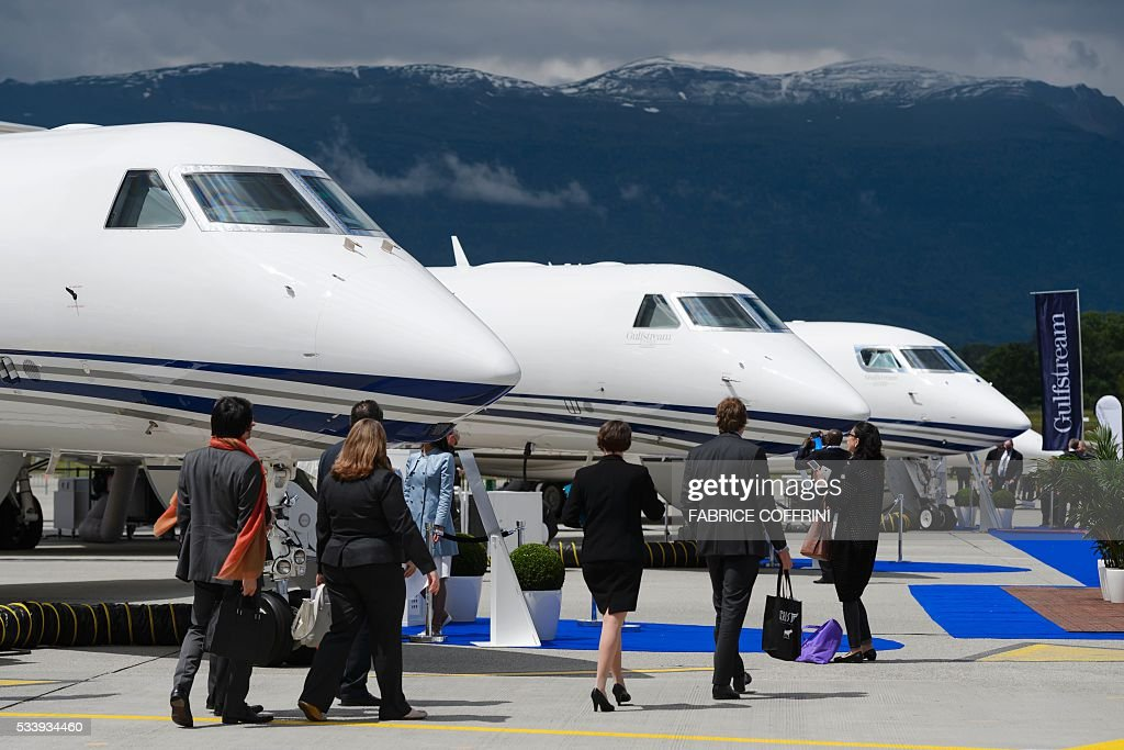 People visit the static stand of US bussiness jet maker Gulfstream Aerospace Corporation during the European Business Aviation Convention & Exhibition (EBACE) on May 24, 2016 in Geneva. COFFRINI