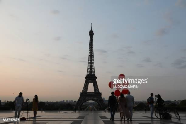 People visit the Trocadero Plaza to take souvenir pictures at sunrise with the Eiffel Tower in the background on August 25 in Paris / AFP PHOTO /...