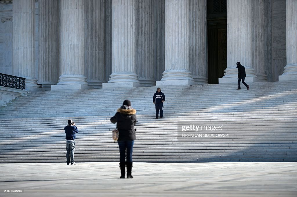 People visit the US Supreme Court February 14, 2016 in Washington. Justice Antonin Scalia, a towering conservative voice on the US Supreme Court, has died at the age of 79, triggering a political showdown over his succession in the run-up to the presidential election. President Barack Obama ordered flags to fly at half-staff across the United States until the long-serving justice, first appointed by Ronald Reagan in 1986, is laid to rest. / AFP / Brendan Smialowski