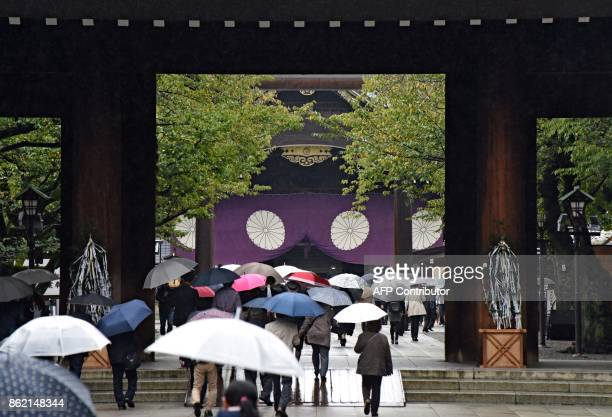 People visit to the controversial Yasukuni Shrine in Tokyo on October 17 2017 Abe sent a ritual offering to a controversial war shrine on October 17...