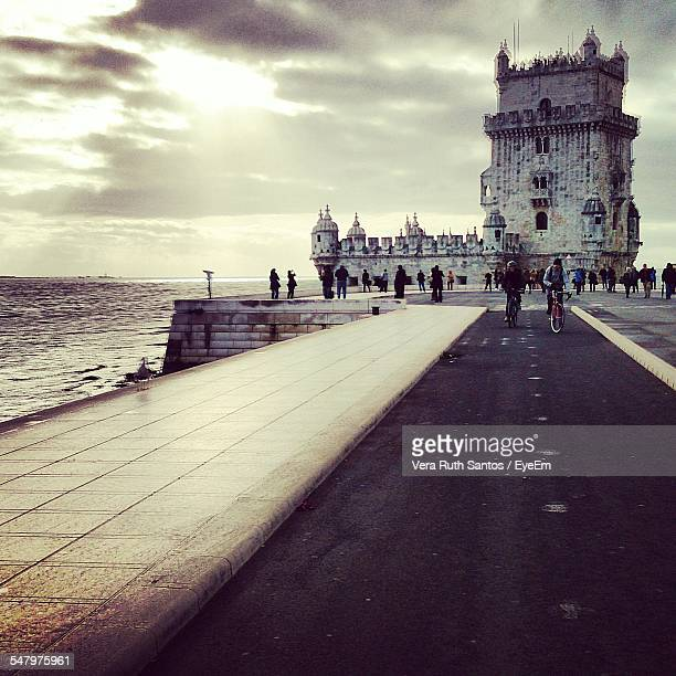 People Visiting Belem Tower Against Cloudy Sky