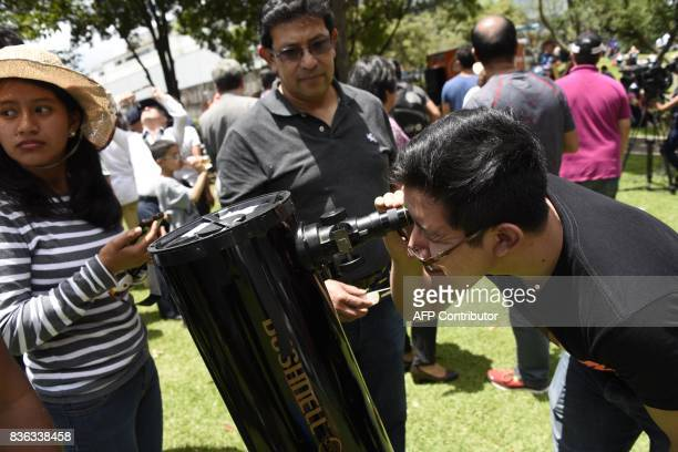 People visiting to Miraflores Museum watch the partial solar eclipse through a telescope in Guatemala City on August 21 2017 / AFP PHOTO / JOHAN...