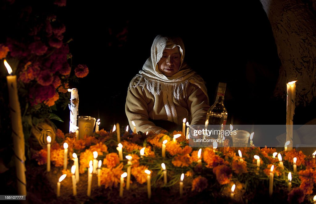 People visits the grave of relatives with flowers and candles during of the Day of the Dead celebrations, in Santa Maria Atzompa, Oaxaca, Mexico, on November 1, 2012