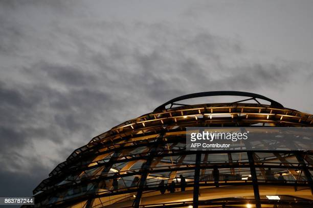 People vist the glass dome roof of the Reichstag which houses the Bundestag lower house of parliament as members of the delegations of the CDU/CSU...