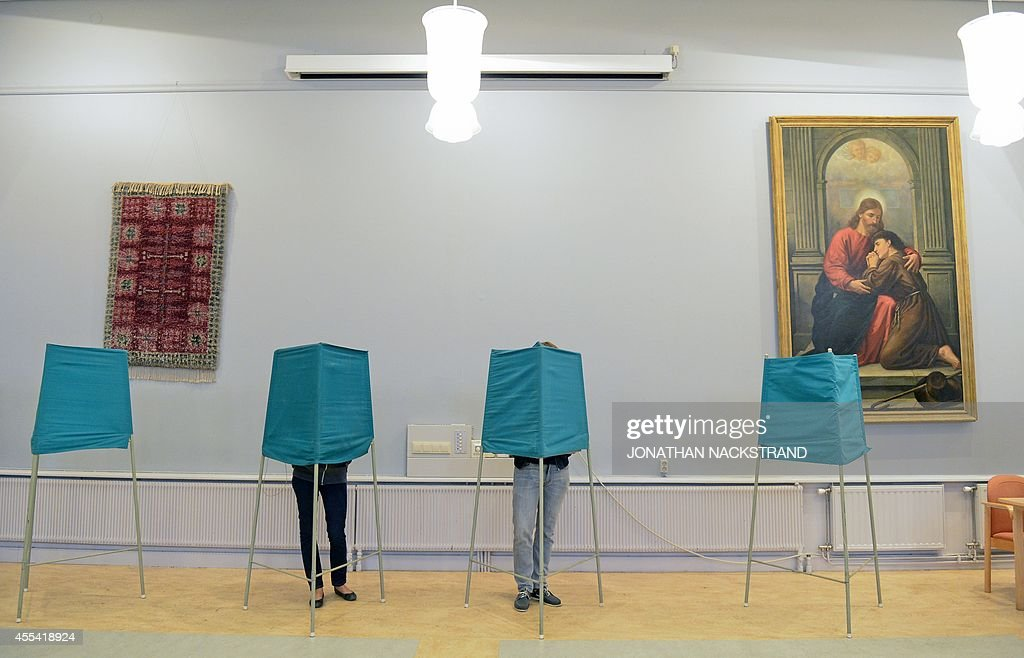 People vote at a polling station during the Swedish general elections in Stockholm on September 14, 2014. Polling booths opened at 0600 GMT and will close 12 hours later, determining the allocation of 349 seats in the Nordic country's legislature, the Riksdag.
