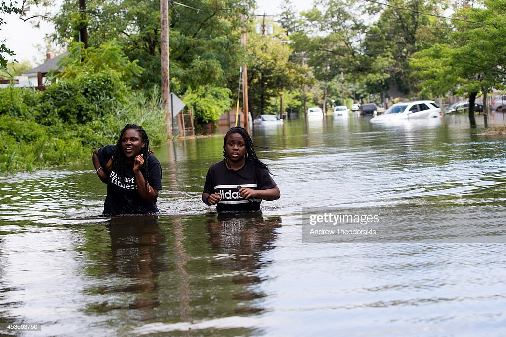 People wade along Reddington St. following heavy rains and flash flooding on August 13, 2014 in Bayshore, New York. The south shore of Long Island along with the tri-state region saw record setting rain that caused roads to flood entrapping some motorists.