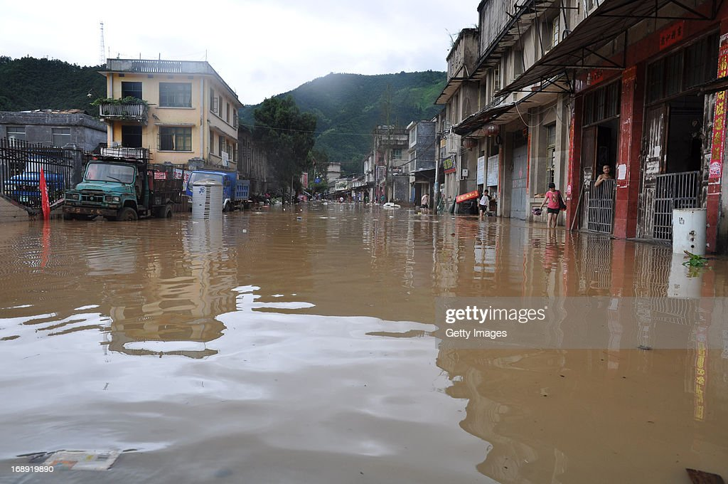People wade in a flooded street on May 16, 2013 in Jianghua County, China. A round of rainstorms hit South China since Tuesday, leaving 33 people dead and 12 missing.