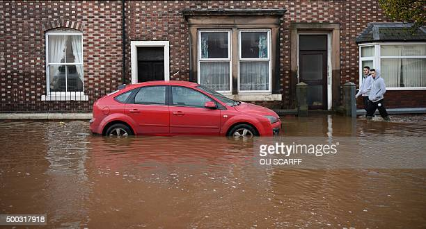 People wade in flood water as they pass a submerged vehicle and houses in Carlisle north west England on December 7 after heavy flooding caused by...