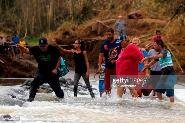 People wade into the San Lorenzo River after a bridge was swept away by Hurricane Maria in Morovis Puerto Rico on September 30 2017 US military and...