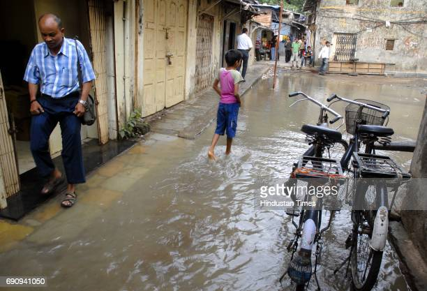 People wade through a flooded bylane in Lower Parel as a water pipe near the Jiva Masoom chawl burst while it was being repaired According to the...
