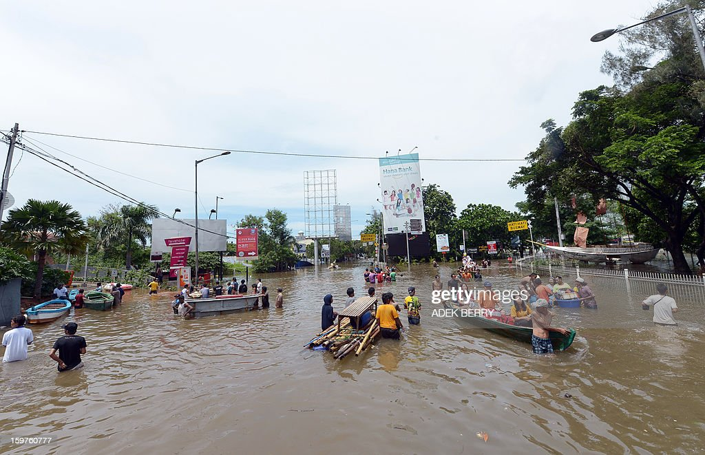 People wade through a flooded street at a luxury housing complex in Jakarta on January 20, 2013. The death toll from floods in Indonesia's capital Jakarta rose to 15 on January 19 after rescuers found another four bodies. The floods are the worst to hit the capital since 2007 and forced 18,000 people from their homes.