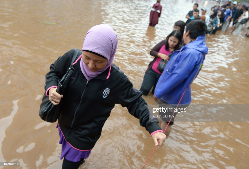 People wade through a flooded street to reach their offices in Jakarta on January 18, 2013. Floods in Indonesia's capital Jakarta have left at least 11 people dead, authorities said on January 18 as murky brown waters submerged parts of the city's business district, causing chaos for a second day.