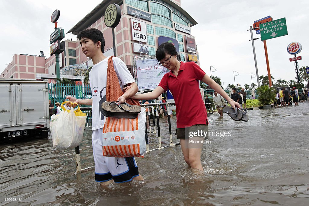 People wade through floodwaters past Citraland shopping mall in Jakarta, Indonesia, on Friday, Jan. 18, 2013. Indonesia declared a state of emergency in Jakarta as flooding brought traffic to a standstill in the city of 9.6 million people and swamped the offices of President Susilo Bambang Yudhoyono. Photograph by: Dimas Ardian/Bloomberg via Getty Images
