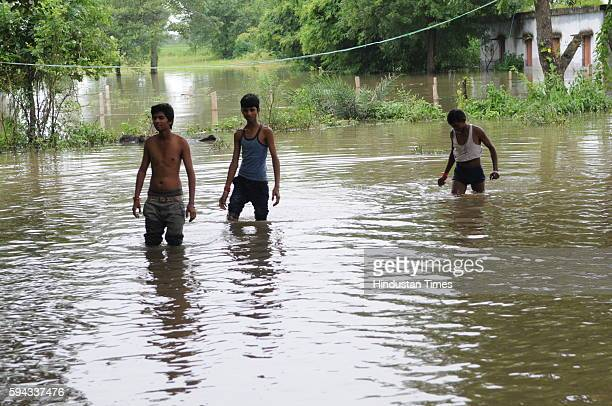 People wade through water as flood like situation is created in village Pipalkhedi after three sluice gates of the Halali dam some 55KM away from...