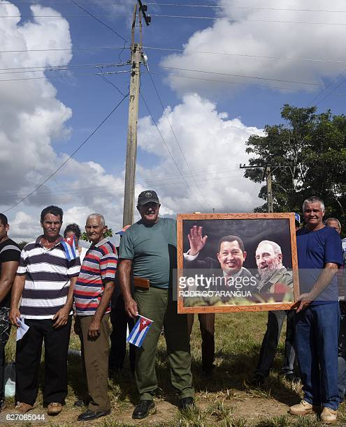 People wait along the Carretera Central to see the convoy carrying the urn with the ashes of late Cuban leader Fidel Castro on December 1 during its...