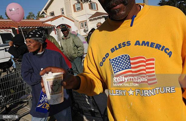 People wait amongst a group of 10000 lowincome and needy people who lined up to receive free Thanksgiving turkeys and fixings distributed by the...