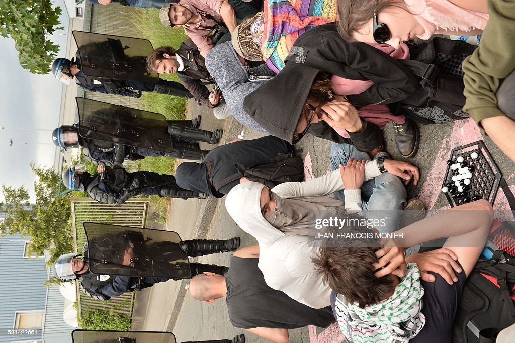 People wait and play next to French riot police during a protest against the government's labour market reforms in Rennes, on May 26, 2016. The French government's labour market proposals, which are designed to make it easier for companies to hire and fire, have sparked a series of nationwide protests and strikes over the past three months.