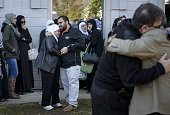 People wait as others participate in a viewing at the Islamic Association of Raleigh North Carolina February 12 2015 before a service for the three...