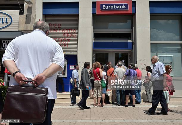 People wait at a bank's ATM while the others speak to an official of the bank in Athens on July 6 2015 More than 61 percent of Greek voters rejected...