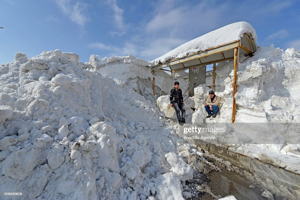 People wait at a bus stop after a heavy snowfall, caused meters of snow depth on the ground in Turkey's Eastern city Bitlis on February 10, 2016. Snowfall covered road, bus stops, traffic signs as well as pavements.