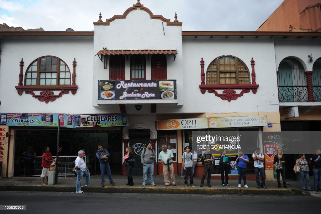 People wait at a bus stop in downtown San Jose, Costa Rica, on November 8, 2012