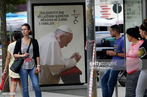 People wait at a bus stop next to a poster showing Pope Francis on September 20 2014 in Tirana one day before Pope Francis' visit Pope Francis will...