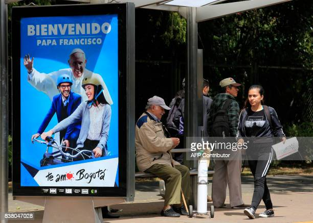 People wait at a bus stop where a sign welcoming Pope Francis is displayed ahead of his upcoming visit in Bogota on August 23 2017 Pope Francis will...
