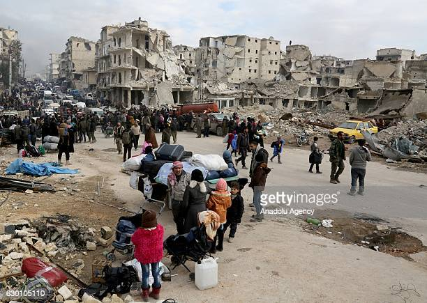 People wait at a crossing point at Amiriyah district of Aleppo Syria on December 16 2016 to evacuate civilians trying to flee from East Aleppo that...