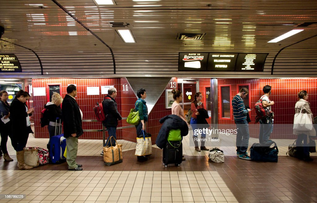 People wait at a gate to board a bus at the New York Port Authority bus terminal in Manhattan on November 21, 2012 in New York City. The Port Authority of New York and New Jersey is expecting to handle a high number of travelers at its hubs, bridges, and tunnels ahead of the Thanksgiving holiday.