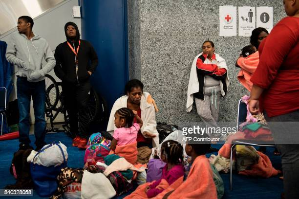 People wait at a shelter in the George R Brown Convention Center during the aftermath of Hurricane Harvey on August 28 2017 in Houston Texas Rescue...