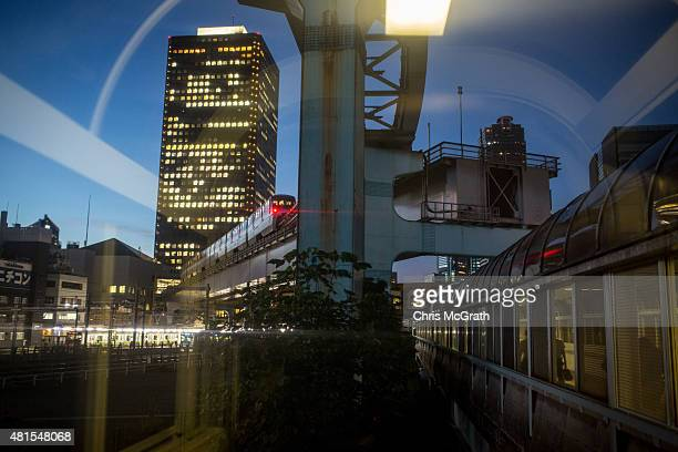 People wait at a train station as a monorail passes by on July 22 2015 in Tokyo Japan