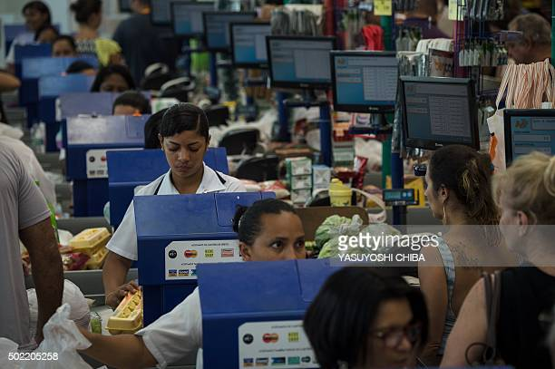 People wait at the checkouts of a supermarket in Rio de Janeiro Brazil on December 21 as they shop for groceries for Christmas AFP PHOTO / YASUYOSHI...