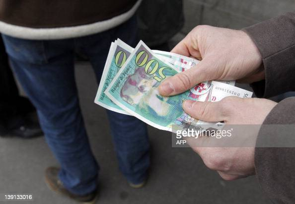 People wait at the counter in a branch of the Banque de France in Paris on February 16 2012 to convert French old banknotes in francs to euros...