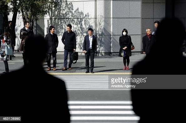 People wait at the crosswalk of the financial and business of Tokyo Japan on February 10 2015 Japanese Prime Minister Shinzo Abe want to revitalise...