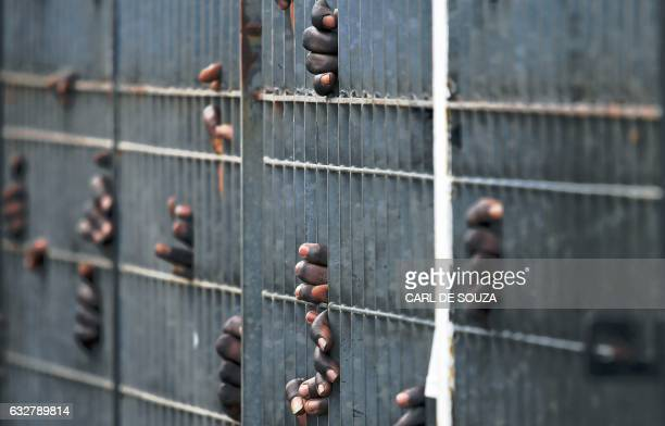 TOPSHOT People wait at the gates for the arrival of President Adama Barrow at the airport in Banjul on January 26 2017 Jubilant Gambians on Janauary...