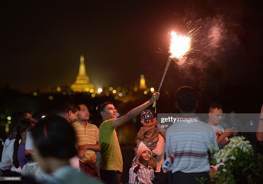 People wait before the countdown to the New Year near the Shwe Da Gon pagoda and Kandawgyi Lake in Yangon on December 31, 2012. Some 50,000 people were expected to gather at the revered golden Shwedagon Pagoda in Yangon for the city's first public countdown to the New Year and fireworks. AFP PHOTO / Ye Aung Thu