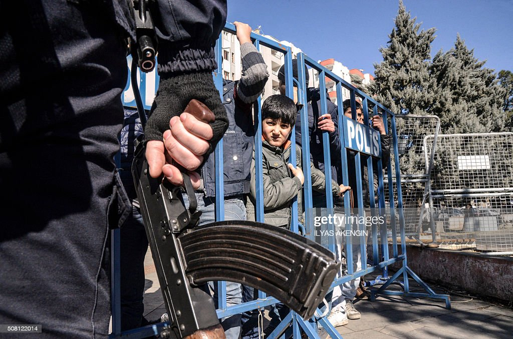 TOPSHOT People wait behind a police barricade near the Sur district of Diyarbakir on February 3 2016 Vowing to flush out the Kurdistan Worker's Party...